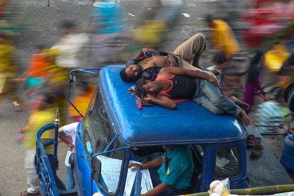 Workers of the police vehicle sleep on its roof in Dhaka, Bangladesh.